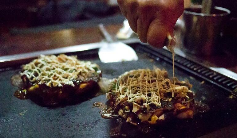 Der Koch gibt dem Okonomiyaki den letzten Schliff mit ein wenig Mayonnaise! - Flickr: Hajime Nagahata